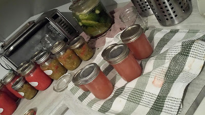 jars of canned produce and croc of pickles