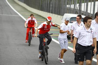 Фелипе Масса едет на велосипеде и толкает Михаэля Шумахера на Гран-при Бразилии 2010