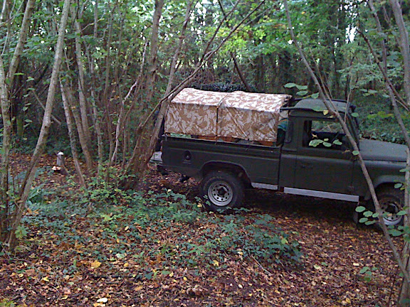 The Landrover is almost completely camouflaged with the mix of green and autumn leaf colours...