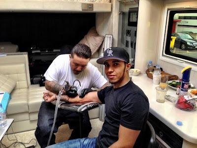 художник Лукас Подольски делает татуировку Льюису Хэмилтону на правой руке 22 февраля 2013