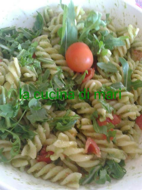 pasta fredda con pesto di rucola,  pomodorini,  rucola e scaglie di grana