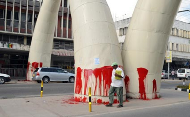 A Mombasa resident walks by the decorative elephant tusks located on Moi Avenue in Kenya's coastal city of Mombasa. The monument was defaced by activists on 3 October 2014, who smeared it with dripping red paint and the phrase, 'Mombasa Not 4 Ivory Export'. Photo: Kevin Odit