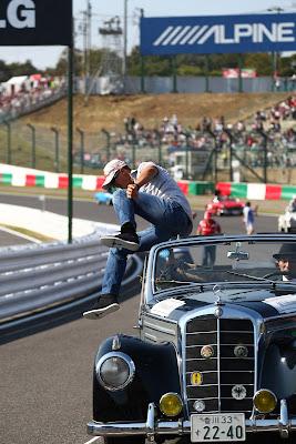 Михаэль Шумахер выпрыгивает из машины во время парада пилотов на Сузуке на Гран-при Японии 2011