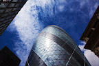 "30 St Mary Axe, also known as ""the Gherkin"", is a skyscraper  in London's financial district completed in December 2003, with height of 180 meters and 41 floors."