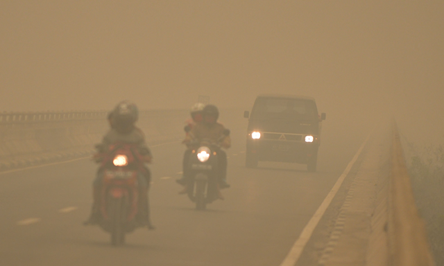 Commuters drive through thick haze in Tumbang Nusa, Central Kalimantan, on 25 October 2015. Indonesia has put warships on standby to evacuate people affected by acrid haze. Photo: Bay Ismoyo / AFP / Getty Images