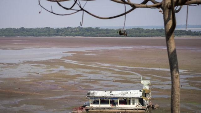 A former floating house now stranded because of low water levels is seen on the bed of the Aleixo Lake, in the rural area of Manaus, Amazonas, Brazil, on 23 October 2015. Photo: Raphael Alves / AFP / Getty Images