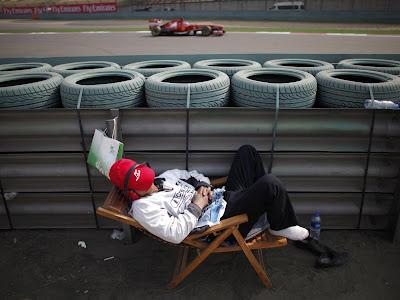 спящий маршал и болид Ferrari на заднем фоне на Гран-при Китая 2013