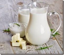 Latte in caraffa, bicchiere, yogurt, formaggio su legno