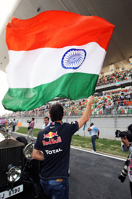 Марк Уэббер размахивает индийским флагом на параде пилотов Гран-при Индии 2011