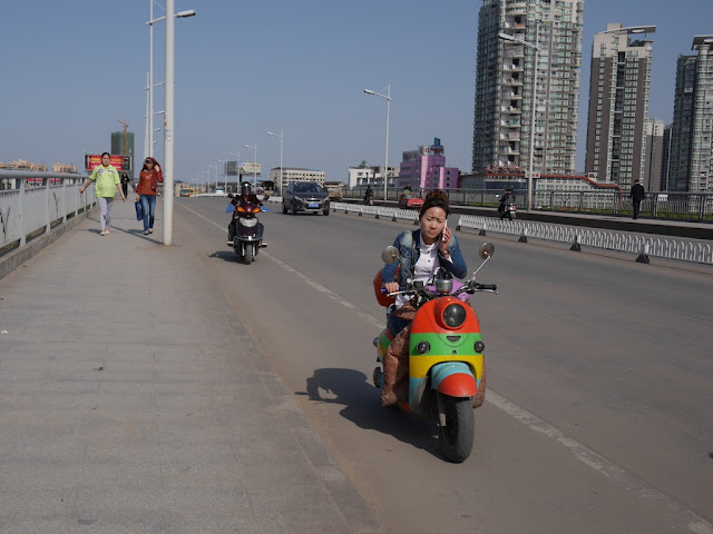woman using a mobile phone while driving a multi-colored motorbike