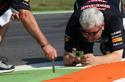 механики Red Bull фотографируют высоту поребриков Монцы с линейкой на Гран-при Италии 2012