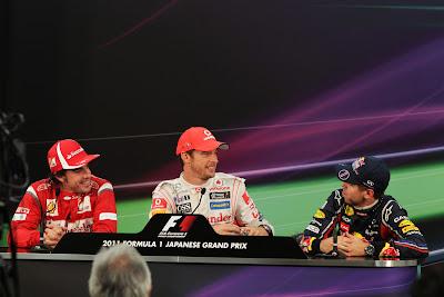 Фернандо Алонсо и Дженсон Баттон смотрят на Себастьяна Феттеля на пресс-конференции после гонки на Гран-при Японии 2011
