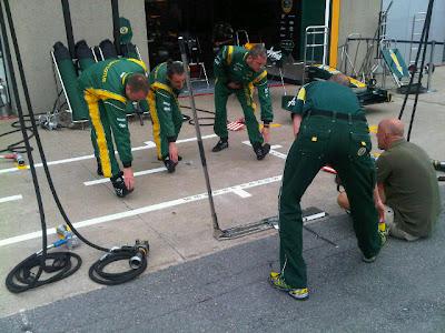 механики Team Lotus разминаются на пит-лейне Монреаля на Гран-при Канады 2011