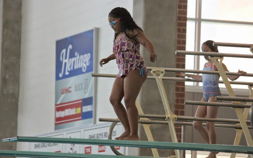 Carefully picking her way to the end of the high diving board.