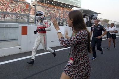 Джессика Мичибата приветствует бегущего по пит-лейну Дженсона Баттона на Гран-при Японии 2011