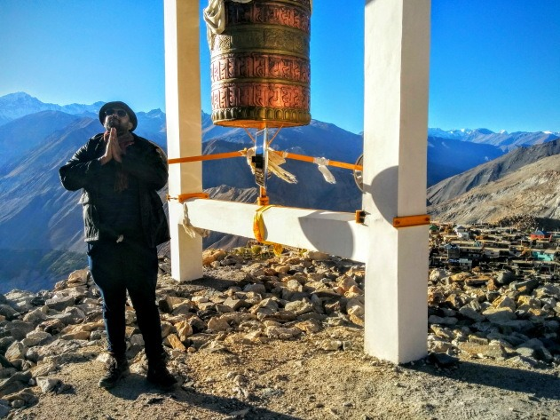 Praying next to a giant prayer wheel at Nako