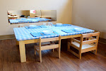 """Instead of high chairs, which make children dependent on adults, our infants take their meals at a low """"weaning table."""" We set it beautifully, with place mats and real dishes. They just love it!"""