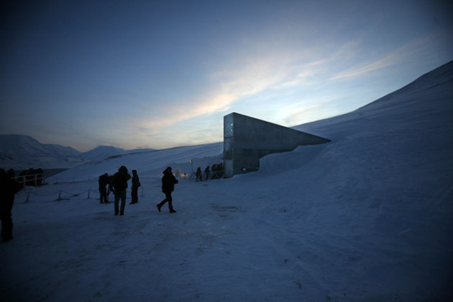 People walk to the entrance of the Svalbard Global Seed Vault. Due to Syria's civil war, the seed vault will now allow a withdrawal of its contents for the first time in its existence. Photo: John McConnico / ASSOCIATED PRESS