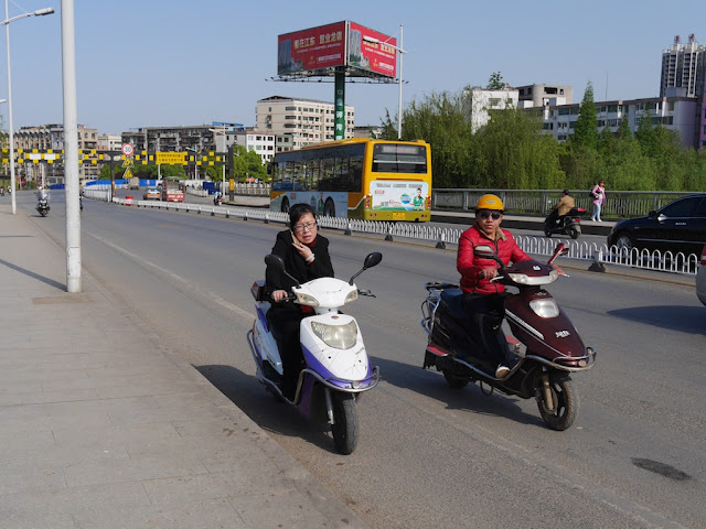 woman holding a mobile phone to her right ear with her left hand while driving a motorbike