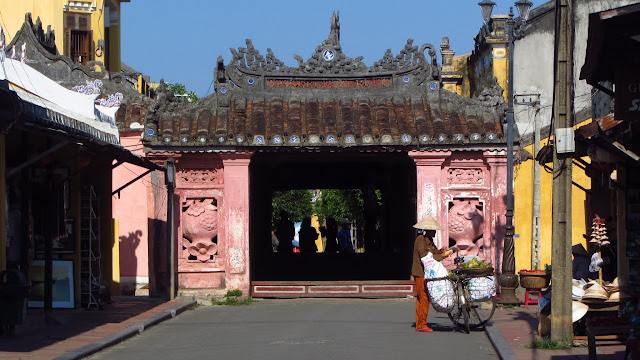 "A merchant with bike and Hoi An's iconic ""Japanese Bridge""."