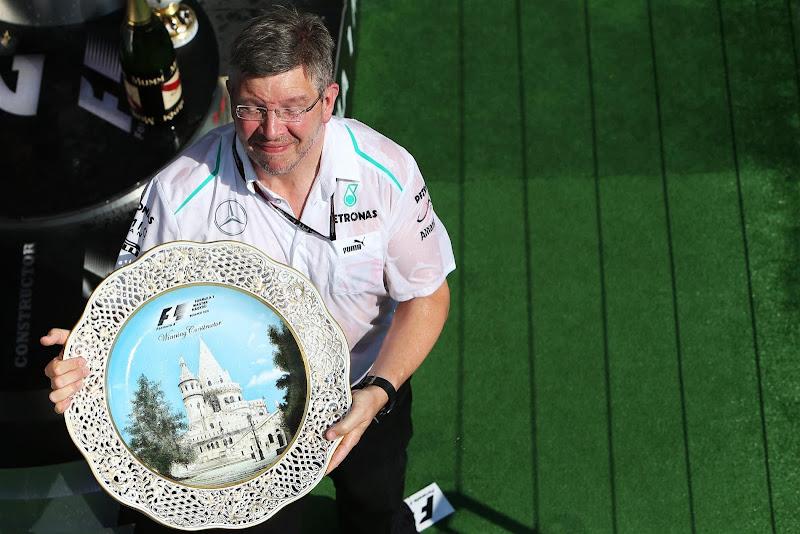 Росс Браун держит победный кубок на подиуме Хунгароринга на Гран-при Венгрии 2013