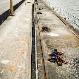 Walking the Dam by Rob Heber - Buildings & Architecture Architectural Detail ( railing, natural light, spillway, curb, architecture, rusty, road, engineering, nature, rusting, metal, flood crontrol, cement, flood gates, rust, water, guard rail, low angle, chains, hand rail, vanishing perspective, lake, concrete, lake water, rusted, outdoors, dam, bridge, design )