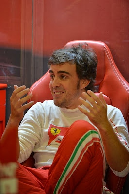 улыбающийся Фернандо Алонсо жестикулирует в боксах на Гран-при Абу-Даби 2013