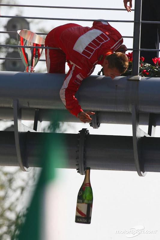 Михаэль Шумахер кидает бутылку шампанского с подиума Гран-при Италии 2006