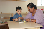 Montessori preschool children receive frequent, individual lessons from their teachers. Here, a preschool boy at our Palos Verdes campus receives a lesson on how to carefully pour water.