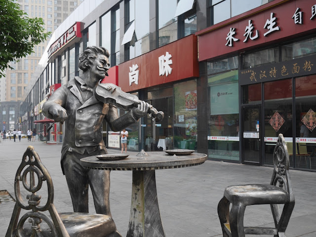 statue of a man playing a violin next to a table and chairs behind Kaifu Wanda Plaza
