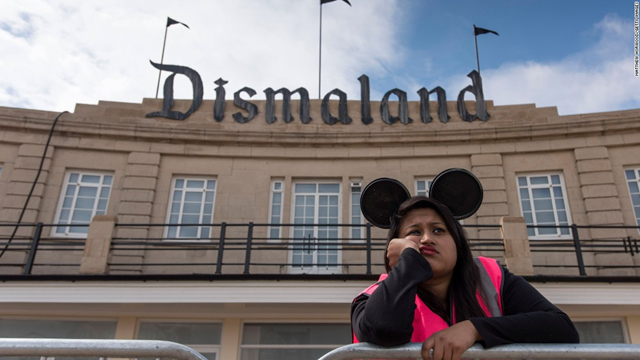 'Welcome to Dismaland,' a dead-eyed girl in Mickey Mouse ears greets at the gates of the old public pool. Dismaland is the latest exhibition from Banksy, the art world's favorite agent provocateur. Billed as a 'bemusement park'. Photo: CNN
