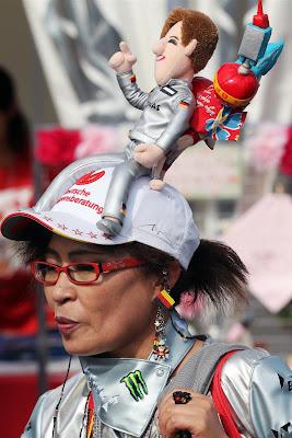 болельщица Михаэля Шумахера с куклой пилота на кепке на Гран-при Японии 2012