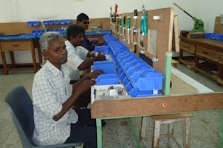 Three workers at the Tamilnadu Blind-Lead facility sit assembling labeler components, which they have fabricated from raw materials. (Front to back: Panneer Selvam, Govindaraj, and Chity Babu)