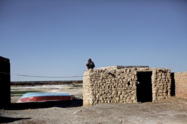 Iranian boys sit on the roof of a mud-house in the village of Adimi situated in the once exceptional wetlands of Lake Hamoon, now sand-baked earth. Photo: AFP
