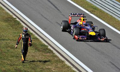 Себастьян Феттель на Red Bull проезжает мимо гуляющего по трассе Кими Райкконена во время первой сессии свободных заездов на Гран-при Кореи 2013