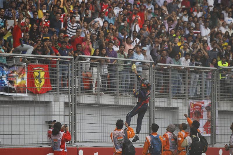Себастьян Феттель залазит на ограждение и кидает перчатки болельщикам после финиша Гран-при Индии 2013