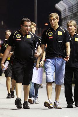 веселый Виталий Петров идет с механиками по трассе Сингапура на Гран-при Сингапура 2011