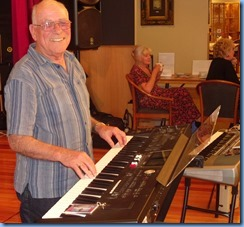 Laurie Conder playing his Roland keyboard for us. In the background, Delyse Whowood and Margaret Black are dutifully manning the raffle and information desk.