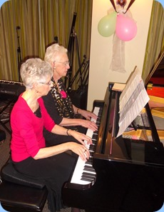 Patricia and Dorothy Waddel playing a duet on the grand piano.