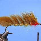 4. Przywiązuję pióra przy uszku haczyka pozostawiając miejsce na jeżynkę. Owalną lametą przewijam pióra prowadząc ją tak, aby do tułowia przylegały odcinki stosin pozbawionych promieni, promienie pozostawione powinny odstawać ku górze tworząc charakterystyczny grzebień.