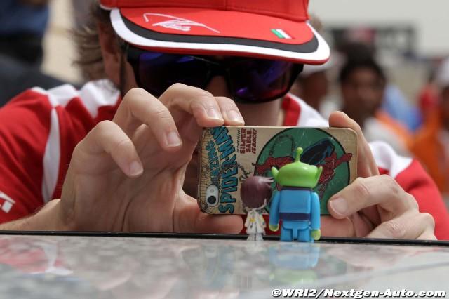 Фернандо Алонсо фотографирует фигурки на Гран-при Бахрейна 2012
