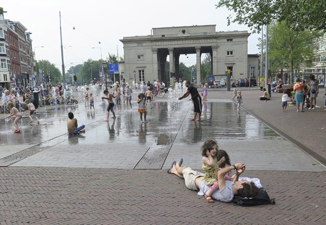 People cool off in the water fountains at Haarlemmerplein square in Amsterdam, the Netherlands, on Thursday, 2 July 2015. It was the warmest July day since records began in the Netherlands. Phot: Margriet Faber / AP Photo