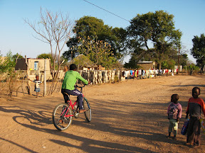 """A boy riding a bicycle, considered a """"privileged"""" mode of transport for village life. Nyiko Ubisi Transport I go to school but my road is to (too) long to go school. If I going to school I walking 20 minets after school im going to home im walking 30 minets because I walking to slow I take a long time. If I going im pass the spazet shop (name for a very small shop that sells basic goods) I go I cross I look north then I go to home."""
