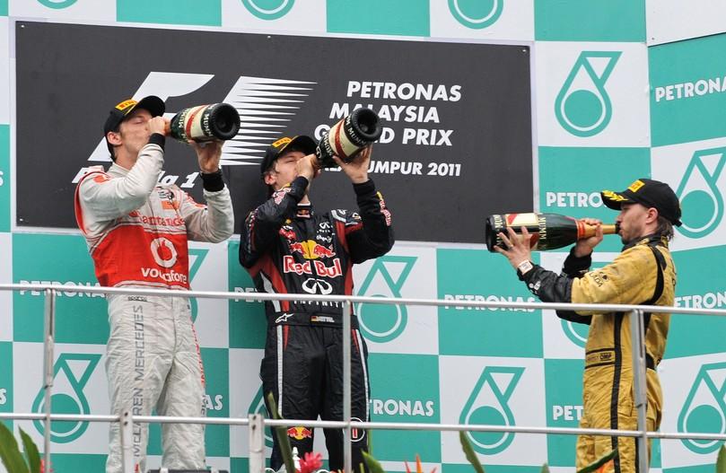 Дженсон Баттон, Себастьян Феттель и Ник Хайдфельд пьют шампанское на подиуме Куала-Лумпура на Гран-при Малайзии 2011
