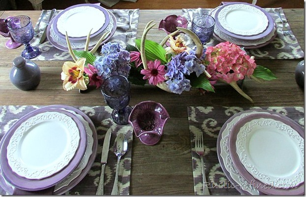 Gorgeous purple tablescape with antlers, fresh flowers on a barn wood dining table