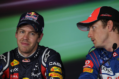 Дженсон Баттон шепчет что-то Себастьяну Феттелю на пресс-конференции после квалификации на Гран-при Абу-Даби 2011