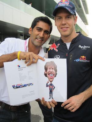 Себастьян Феттель фотографируется со своей карикатурой из книжки VROOOM на Гран-при Индии 2011
