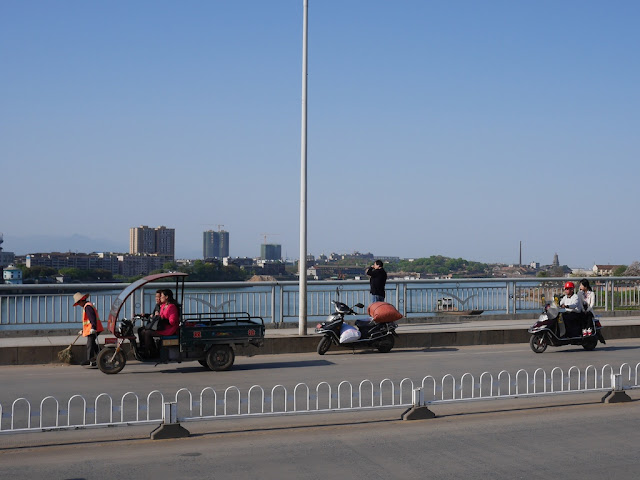 man looking over the railing of a bridge while speaking on a mobile phone and his motorbike parked in a bike lane