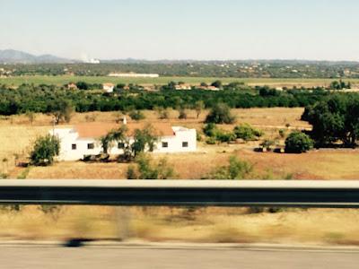 Et hvitt hus i et grønt landskap sett fra motorveien.