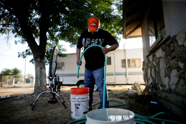 In this 30 June 2015 photo, Tino Lozano looks into a bucket as the last of his available well water drips from a hose in front of his home in the community of Okieville, on the outskirts of Tulare, California. 'There it goes. That was all,' said Lozano, masking his desperation with a smile. 'That's how we do it in Okieville now.' Millions of Californians are being inconvenienced in this fourth year of drought, but it's worse in places like Okieville, where wells have gone dry for many in the Central Valley community which was built by refugees from Oklahoma's epic Dust Bowl drought. Photo: Gregory Bull / AP Photo